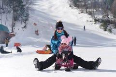 一个年轻母亲在与她的一点女儿的山旅行在一个晴朗的冬天 免版税库存照片