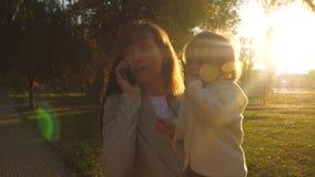 一个年轻母亲在智能手机谈话并且运载她的胳膊的一个小女儿 母亲和一点女儿走 股票视频