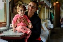 一个年轻母亲在玻璃旅行与一个美妙地美丽的女儿一起 免版税库存照片