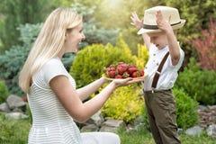 一个年轻母亲对待她的小儿子成熟芬芳草莓 库存图片