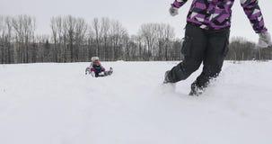 一个年轻母亲拉扯与两个孩子的一个雪橇白色雪的 股票视频