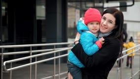 一个年轻母亲的画象有一个婴孩的她的胳膊的 股票视频