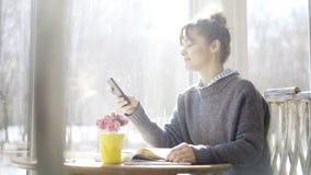 一个年轻深色的女孩看她的在咖啡馆的电话 库存照片