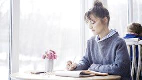 一个年轻深色的女孩读在咖啡馆的一个笔记本 免版税库存照片