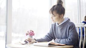 一个年轻深色的女孩读在咖啡馆的一个笔记本 免版税库存图片