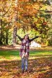 一个年轻深色的妇女投掷的秋天叶子到空气里 库存照片