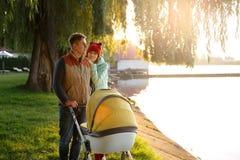 一个年轻爱恋的家庭由有婴儿推车的湖走 微笑在秋天公园做父母加上婴孩摇篮车 爱,父母身分, f 免版税图库摄影