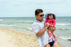 一个年轻父亲握他的在海滩的女儿` s手 免版税库存照片