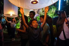 一个年轻男孩在清迈,泰国发布一个浮动灯笼 图库摄影