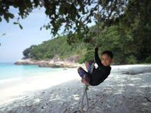 一个年轻男孩垂悬在绳索由海滩 图库摄影