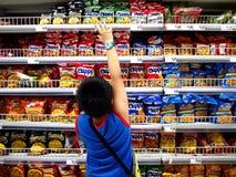 一个年轻男孩读点心的标签在超级市场里面的 免版税库存照片