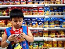 一个年轻男孩读点心的标签在超级市场里面的 图库摄影