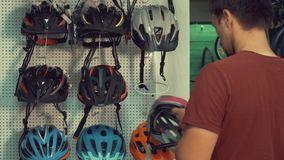 一个年轻白种人人在一个立场附近站立在领袖保护部门的一家自行车商店 选择自行车 股票录像