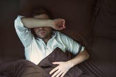 一个年轻白种人人的画象从睡觉的在一张黑暗的床上上 免版税库存照片