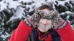 一个年轻白种人可爱的女孩的接近的画象红色外套的在看直接对照相机和摆在展示的冬天大 股票录像
