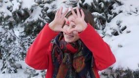 一个年轻白种人可爱的女孩的画象红色外套的在看直接对照相机和摆在展示的冬天大心脏fr 股票录像
