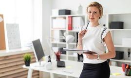 一个年轻白肤金发的女孩在一张桌附近站立在办公室并且拿着文件和一支铅笔在她的手上 库存图片
