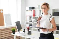 一个年轻白肤金发的女孩在一张桌附近站立在办公室并且拿着文件和一支铅笔在她的手上 库存照片