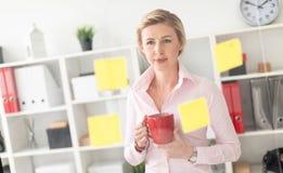一个年轻白肤金发的女孩在办公室在她的手上站立在有贴纸的一个透明委员会旁边并且拿着一个红色杯子 库存照片