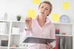 一个年轻白肤金发的女孩在办公室站立在有贴纸的一个透明委员会旁边并且拿着文件和铅笔  图库摄影