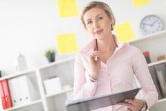 一个年轻白肤金发的女孩在办公室站立在有贴纸的一个透明委员会旁边并且拿着文件和铅笔  免版税库存照片