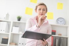 一个年轻白肤金发的女孩在办公室站立在有贴纸的一个透明委员会旁边并且拿着文件和铅笔  库存照片