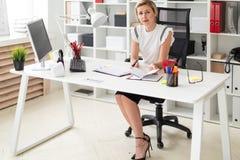 一个年轻白肤金发的女孩在她的手上坐在一张计算机书桌在办公室,拿着一支铅笔和与文件一起使用 免版税库存图片