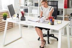 一个年轻白肤金发的女孩在她的手上坐在一张计算机书桌在办公室,拿着一支铅笔和与文件一起使用 库存照片
