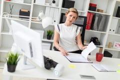 一个年轻白肤金发的女孩在她的手上坐在一张计算机书桌在办公室,拿着一支铅笔和与文件一起使用 免版税库存照片