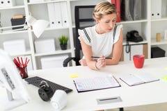 一个年轻白肤金发的女孩在她的手上坐在一张计算机书桌在办公室,拿着一支铅笔和看笔记薄 库存图片