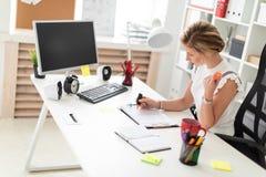 一个年轻白肤金发的女孩在她的手上坐在一张计算机书桌在办公室,拿着橙色标志并且与文件一起使用 免版税库存图片