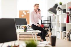 一个年轻白肤金发的女孩在她的手和电话上坐一张桌在办公室,拿着一个红色杯子 库存照片