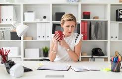 一个年轻白肤金发的女孩坐在一张计算机书桌在办公室,拿着一支铅笔和一个红色杯子在她的手上 免版税库存图片