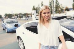 一个年轻白肤金发的女孩看照相机并且在电动车附近微笑 免版税库存照片