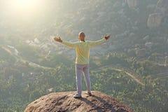 一个年轻秃头人举了他的手并且招呼了在上面的太阳 免版税库存照片