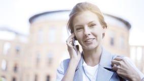 一个年轻繁忙的女孩有一个电话外面户外 免版税图库摄影