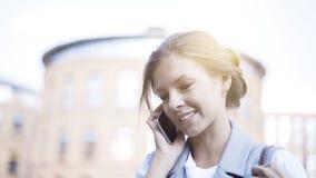 一个年轻繁忙的微笑的女孩有一个电话外面户外 免版税库存照片