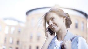 一个年轻繁忙的微笑的女孩有一个电话外面户外 库存图片