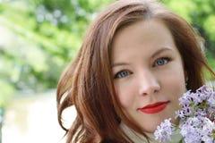 一个年轻红发女孩的美丽的面孔有白色皮肤、蓝眼睛和红色唇膏的在她的嘴唇 丁香分支 免版税库存照片