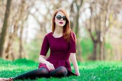 一个年轻红头发人女孩的画象太阳镜的 库存照片