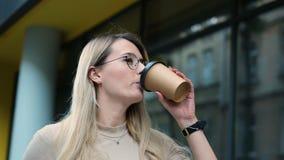 一个年轻美丽的女商人的画象,玻璃的学生,走在城市附近,饮用的咖啡去 影视素材