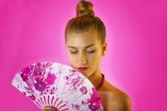 一个年轻美丽的女孩和手特写镜头的色的爱好者的画象有明亮的构成的在桃红色背景 艺妓 免版税库存图片