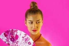 一个年轻美丽的女孩和手特写镜头的色的爱好者的画象有明亮的构成的在桃红色背景 艺妓 库存照片