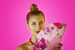一个年轻美丽的女孩和手特写镜头的色的爱好者的画象有明亮的构成的在桃红色背景 艺妓 免版税库存照片