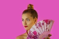 一个年轻美丽的女孩和手特写镜头的色的爱好者的画象有明亮的构成的在桃红色背景 艺妓 库存图片