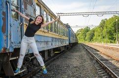 一个年轻美丽的女孩在一个老铁路支架,一列离去的火车的步站立 库存照片
