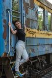 一个年轻美丽的女孩在一个老铁路支架,一列离去的火车的步站立 免版税库存图片
