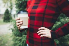 一个年轻美丽的女孩在她的手上拿着一杯咖啡 免版税库存图片