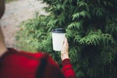 一个年轻美丽的女孩在她的手上拿着一杯咖啡 免版税库存照片