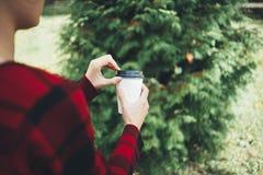 一个年轻美丽的女孩在她的手上拿着一杯咖啡 库存图片